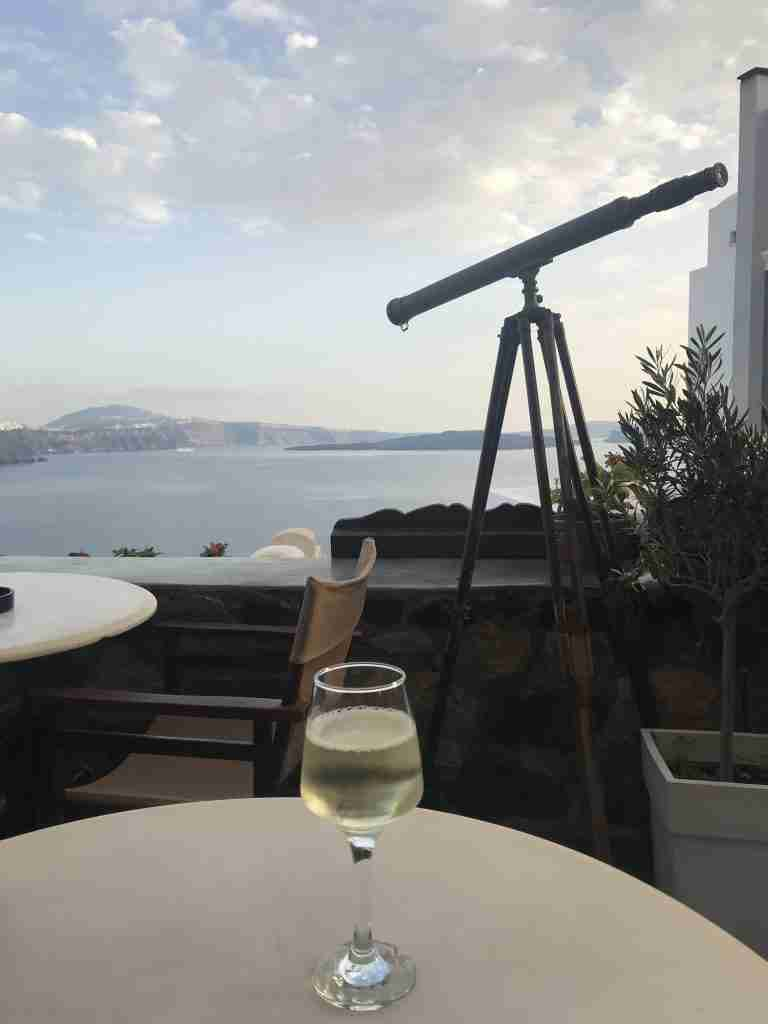 a glass of white wine at a cafe in Santorini Greece with a view of the sea