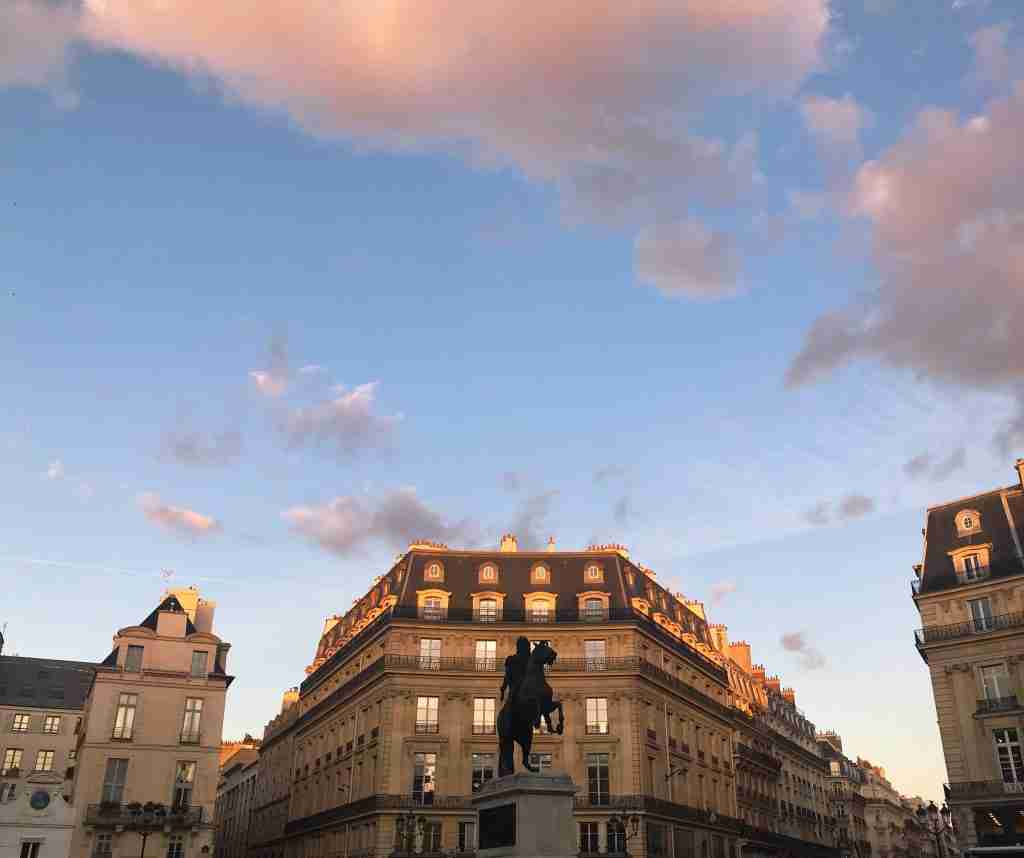 A building and statue in Paris, France during sunset