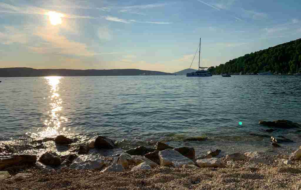Kasjuni beach in Split, Croatia at sunset with a sailboat on the blue Adriatic Sea