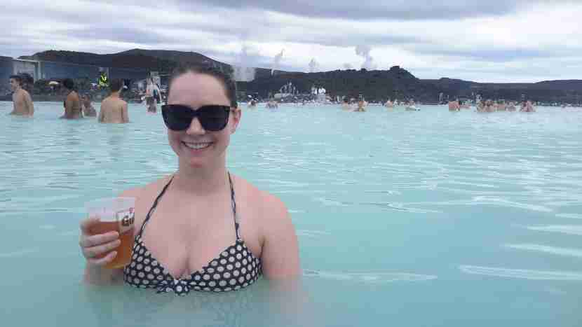 a female solo traveler drinking a beer while soaking in the Blue Lagoon in Iceland