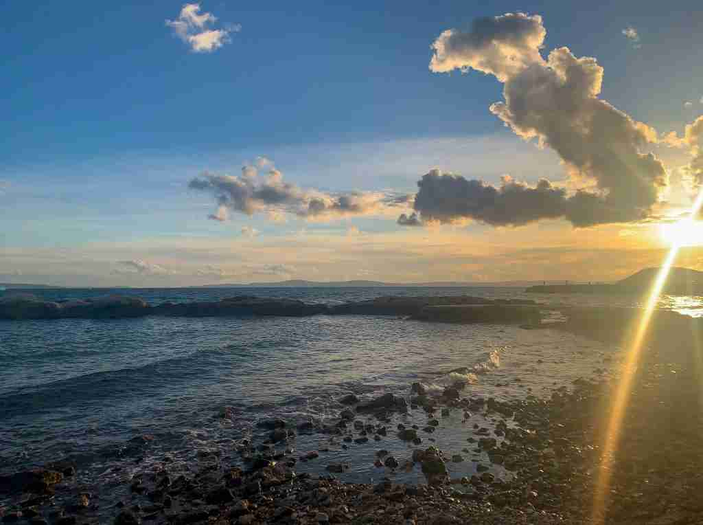 Sunset with clouds at Jezinac Beach in Split, Croatia with waves on the blue Adriatic Sea.